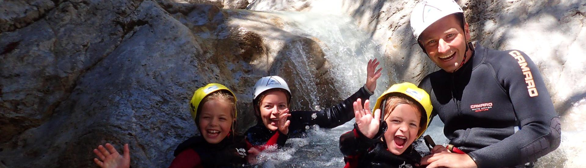 """During the Canyoning """"Family Tour"""" in Rosengartenschlucht, kids are having fun in the natural pool with a certified canyoning guide from WhyNot Adventures."""