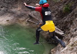 A participant of the Canyoning for Adventurers - Integrale is jumping into a natural pool under the guidance of a state certified canyoning guide from Bergführer Salzburg.