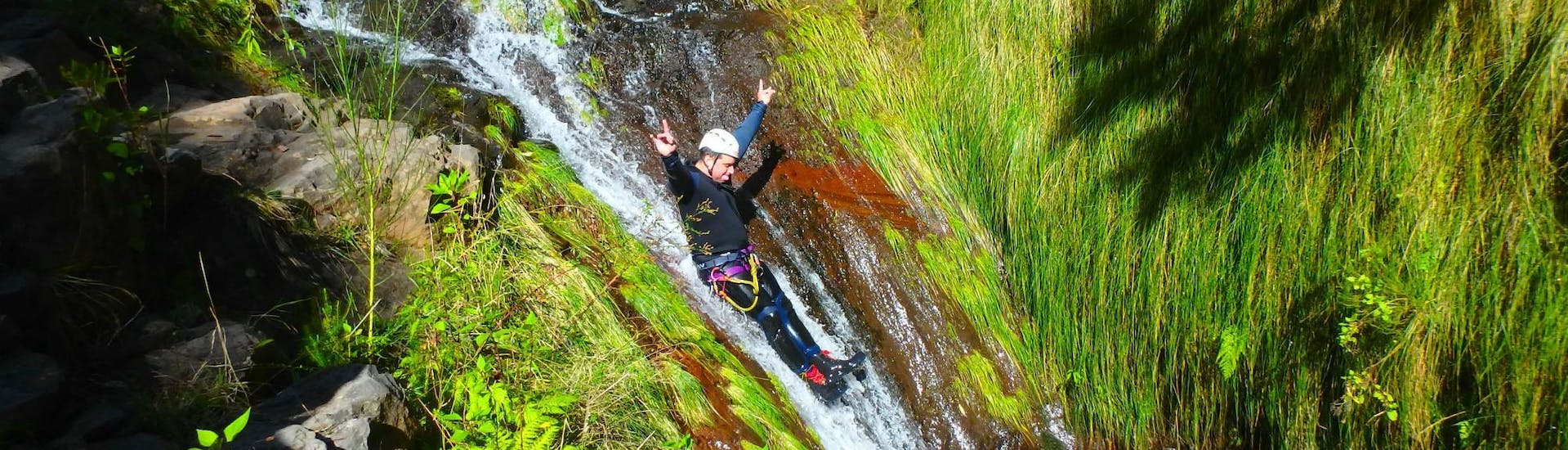 A participant of the Canyoning for Beginners on Madeira with Epic Madeira is having fun as he is sliding down a natural waterslide.