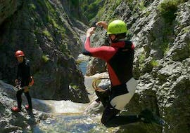 During the Canyoning for Beginners at Lake Sylvenstein, a participant is jumping into a natural pool under the watchful eye of a certified canyoning instructor from Montevia.