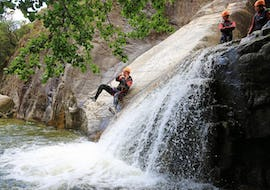 A father is sliding in the Richiusa canyon during his activity of canyoning for families with reves de cimes.