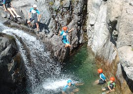 A tourist is jumping and the others are swimming in the canyon du Zoicu during the Canyoning discovery with Canyon Corse.
