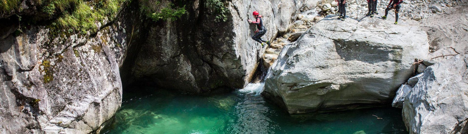 A group of people taking part in the tour Canyoning for Families - Zemmschlucht with Mountain Sports Mayrhofen is jumping into a natural pool of water one by one.