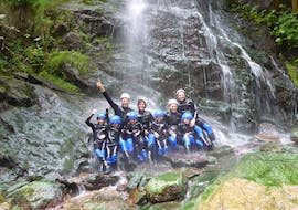 Two families with kids are posing for a picture under a waterfall during their Canyoning for Families in Zillertal with Freiluftakademie.