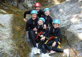 A family is enjoying their canyoning tour for kids in front of a waterfall under the guidance of the experienced team of Frost Rafting & Canyoning Tours.