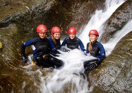 4 girls at the canyoning for Explorers in the beginners canyon enjoying the refreshing waterfall.