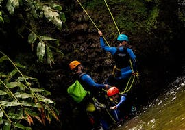 A group of people is abseiling down a rock face during the tour Canyoning in Ribeira dos Caldeirões - Full Day with Picos de Aventura.