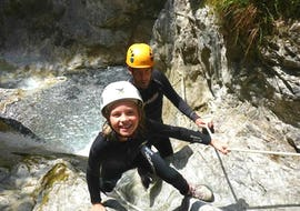 A little girl having fun climbing up a canyon on her Canyoning Tour for Kids and Families at Rosengartenschlucht under the guidance of an experienced instructor from Natur Pur Outdoorsports.