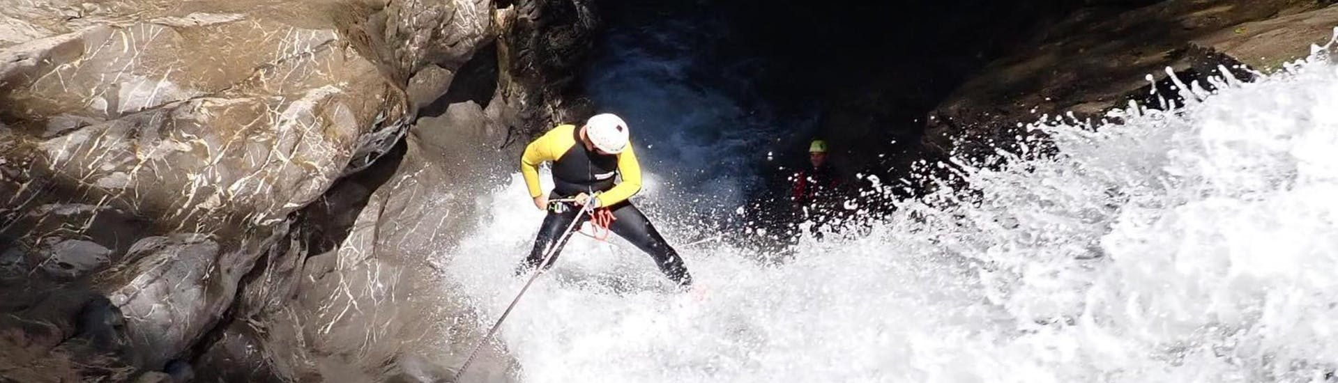 A man is abseiling down a roaring waterfall as he makes his way through the ravine on the tour Canyoning in Schwarzwasserbach for Experienced Canyoneers with canyoning erleben.