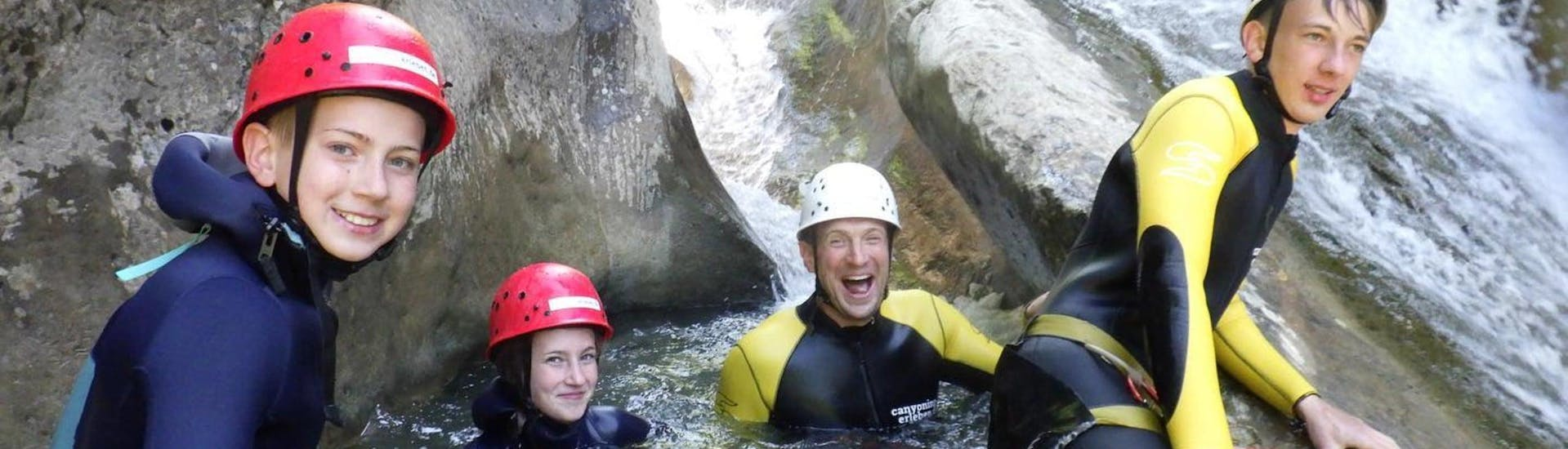 A father and his three children are smiling at the camera as they sit in a rock pool while canyoning in the Allgäu with canyoning erleben.