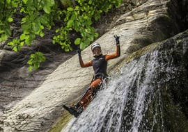 A tourist is sliding in the canyon de la Richiusa during the canyoning tour Sport with canyon corse.