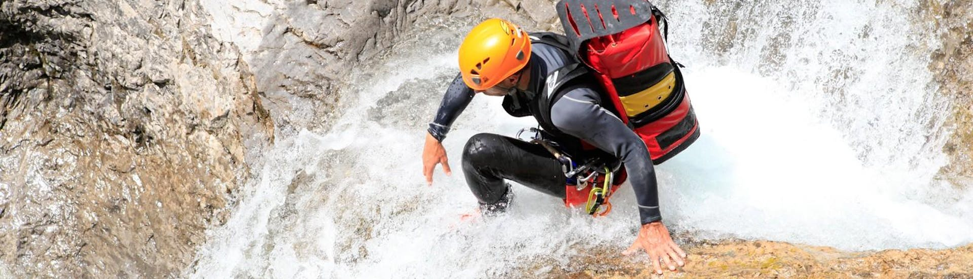 During the Canyoning in the Hochalpschlucht with Fun Rafting Lechtal, a guide is climbing through the water in the gorge.