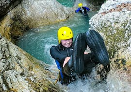 A young woman is sliding down one of the natural waterslides while canyoning in the Sušec Canyon with A2 Rafting Kobarid.