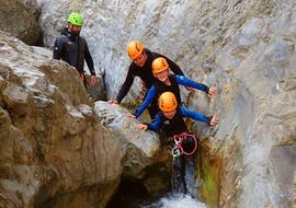Four participants in the Canyoning in Torrente San Michele - Campione Spezial of Skyclimber, are making their way through the rocks of the canyon.