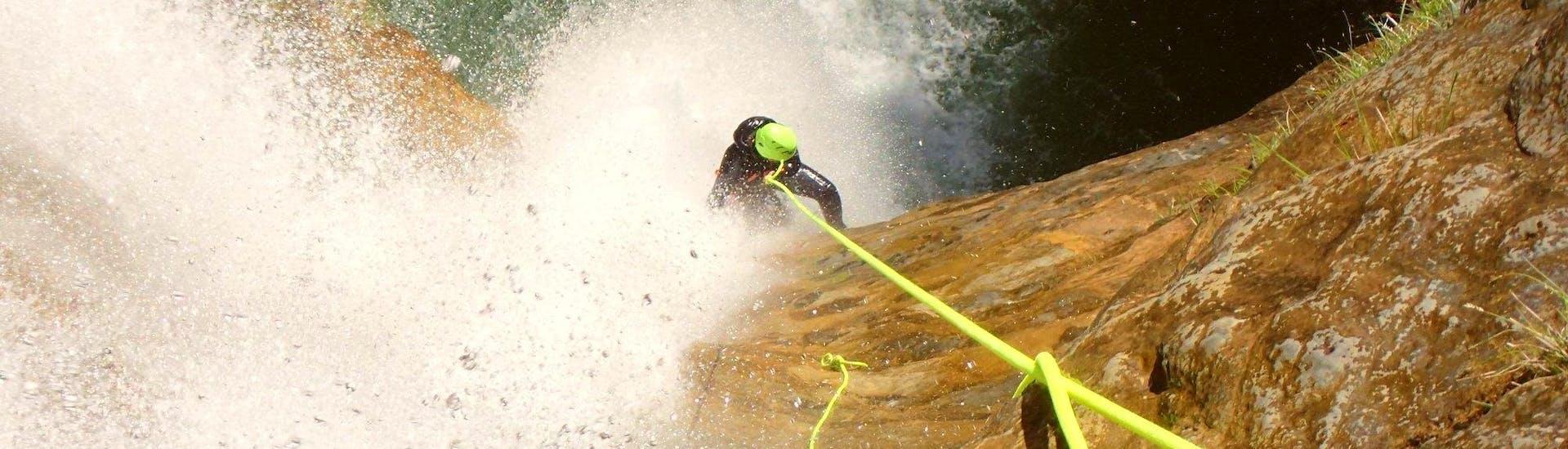 Ein Teilnehmer des Canyoning im Torrente Vione, das von Skyclimber organisiert wurde, steht vor der 45 Meter hohen Abseil.