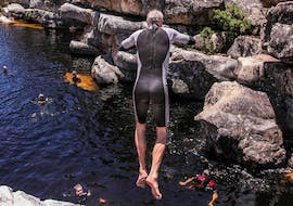 A man is jumping off a rock edge into a natural pool of water while Canyoning in Wellington with Gravity Adventures.