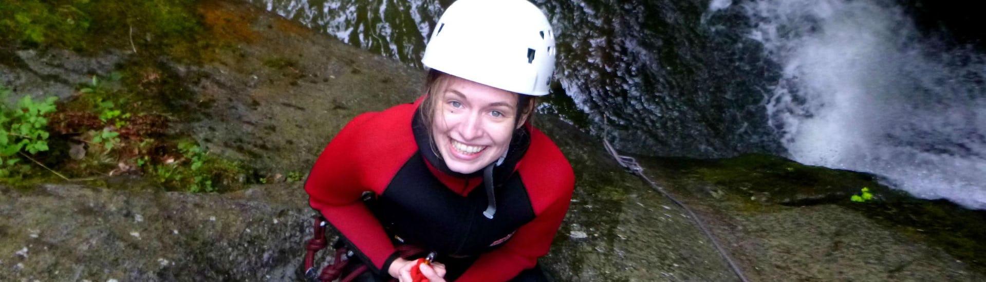 Eine junge Frau seilt sich beim Canyoning im Ötztal entlang einer Felswand ab.