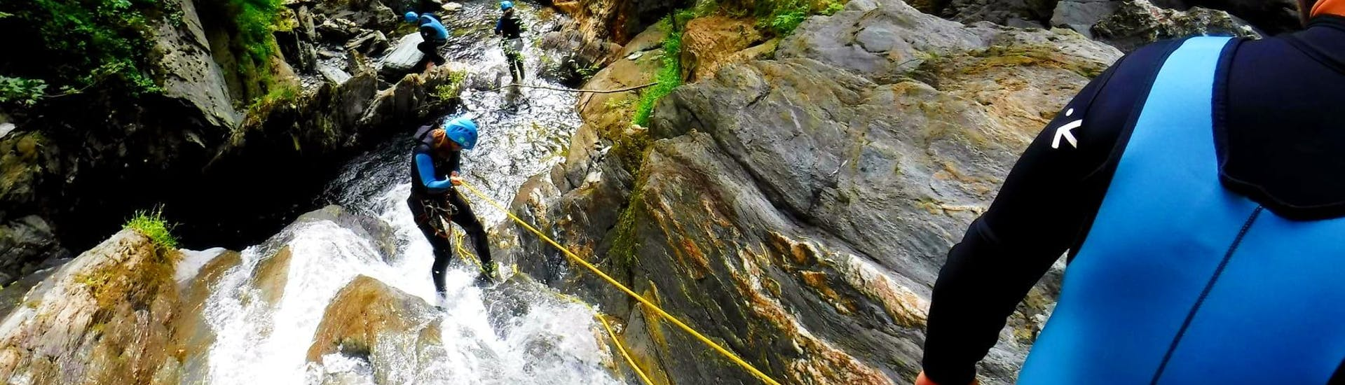 A participant is roping down a waterfall during her Canyoning in the Rettenbach - Online with FROST.