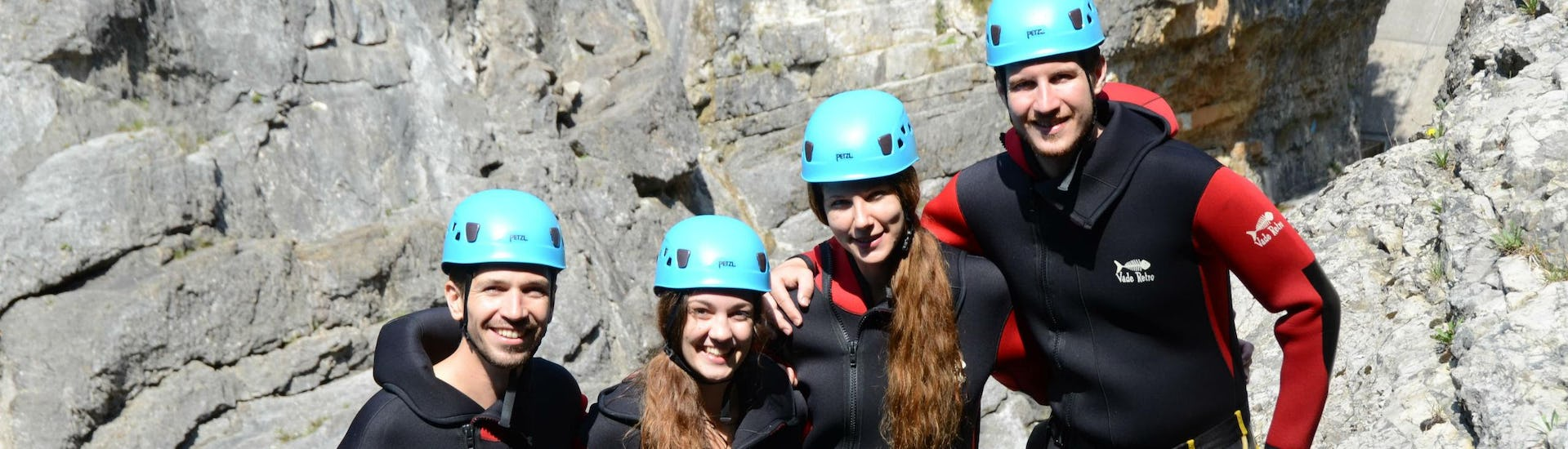 A group of friends is posing for a group photo while on a canyoning tour.