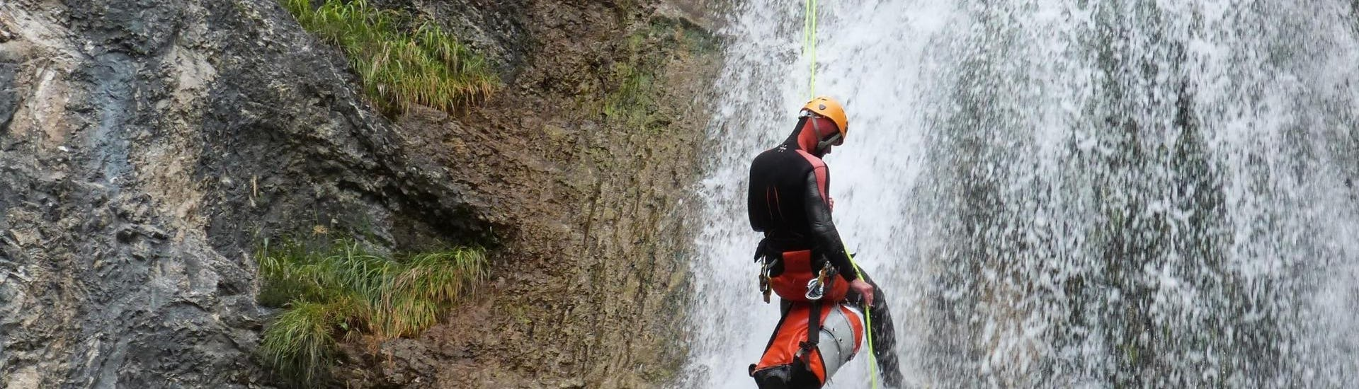 """A guy is abseiling down a rock during the Canyoning """"Redfox Short"""" - Enns Valley under the supervision of an experienced canyoning guide from best adventure company."""