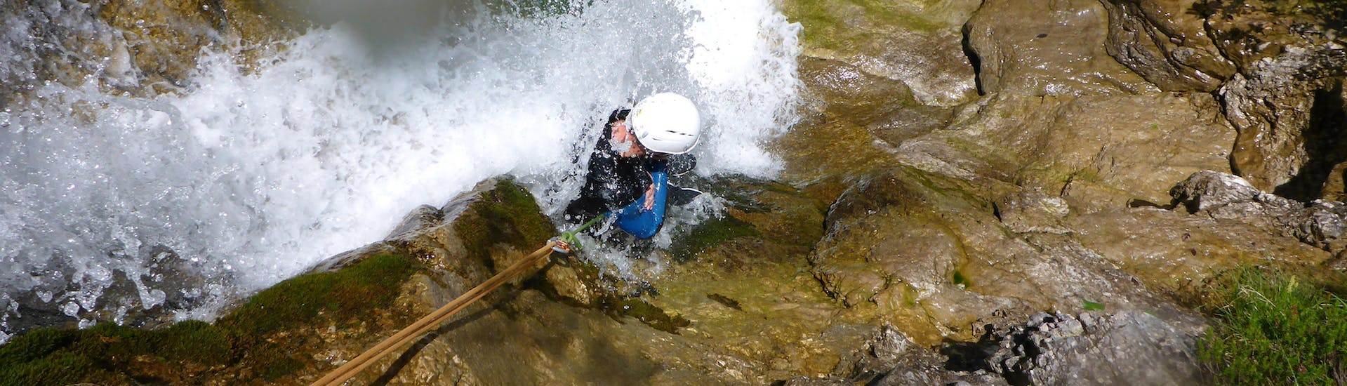 "During Canyoning ""Rocks & Ropes"" for Sportive Beginners with Base Camp, a participant is roping down over a waterfall."