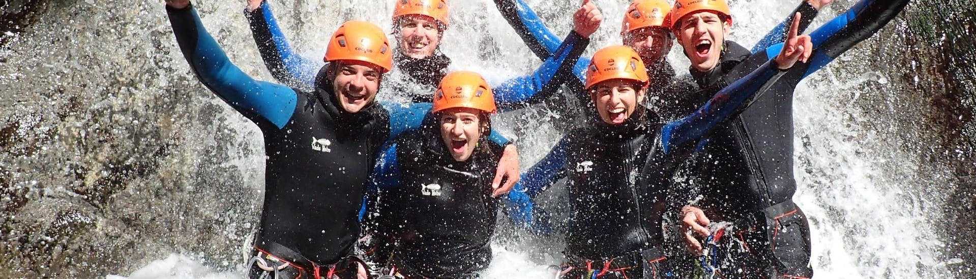 """A group participating to Canyoning """"Sensation"""" - Canyon de Montmin are smiling under the waterfall."""