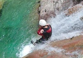 """A man is sliding down a very steep waterslide during the Canyoning """"Sport & Aquatic"""" - Canyon de la Vacca organised by professionals from Acqua et Natura."""