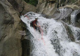 """A canyoning enthusiast is abseiling during their Canyoning """"Sporty Day"""" - Canyon du Haut Chassezac with Les Intraterrestres."""