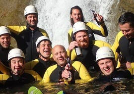 A group of friends is posing for a photo in front of a waterfall during the Canyoning Bachelor Party in the Allgäu with canyoning erleben.