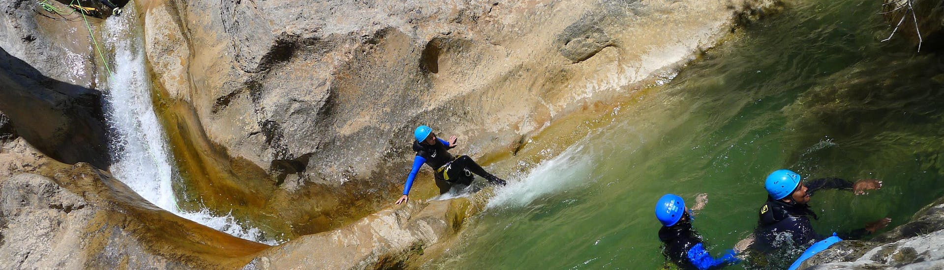 A girl is sliding in the Canyon d'Oô during the Canyoning Technical with H2O vives.