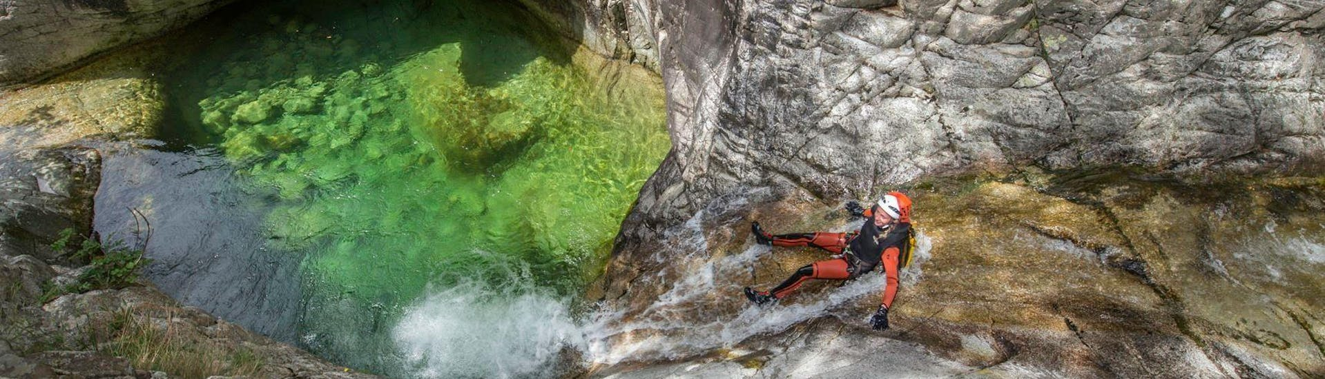 A girl is sliding in the Canyon de Zoicu during the Classic Canyoning activity with their instructor from Canyon Corse.