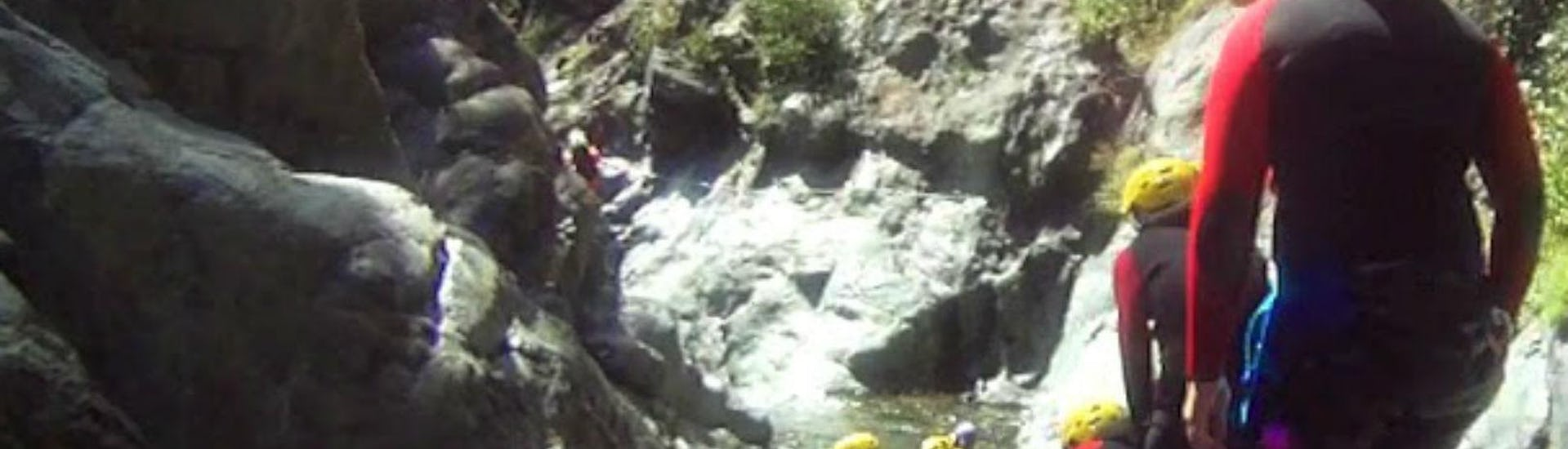 People sliding down a rock in a canyoning course