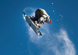 Snowboarder makes a high jump during his Private Snowboarding Lessons for Kids & Adults - All Levels with the ski school Skischule Zugspitze-Grainau.