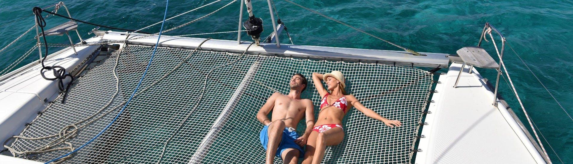 Un couple prend un bain de soleil sur un catamaran.