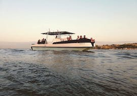 The boat me up catamaran is doing a sunset tour on the Tagus River with many people in Lisbon.
