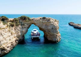 During the catamaran tour from Vilamoura to Caves of Benagil, tourist are passing under a rock formation aboard a modern catamaran from Ocean Quest.