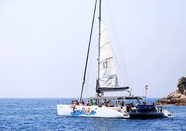 The catamaran from Catamaran Sensations is sailing across the blue waters of the Costa Brava during the Catamaran Trip along Costa Brava with Swimming & Snorkeling.