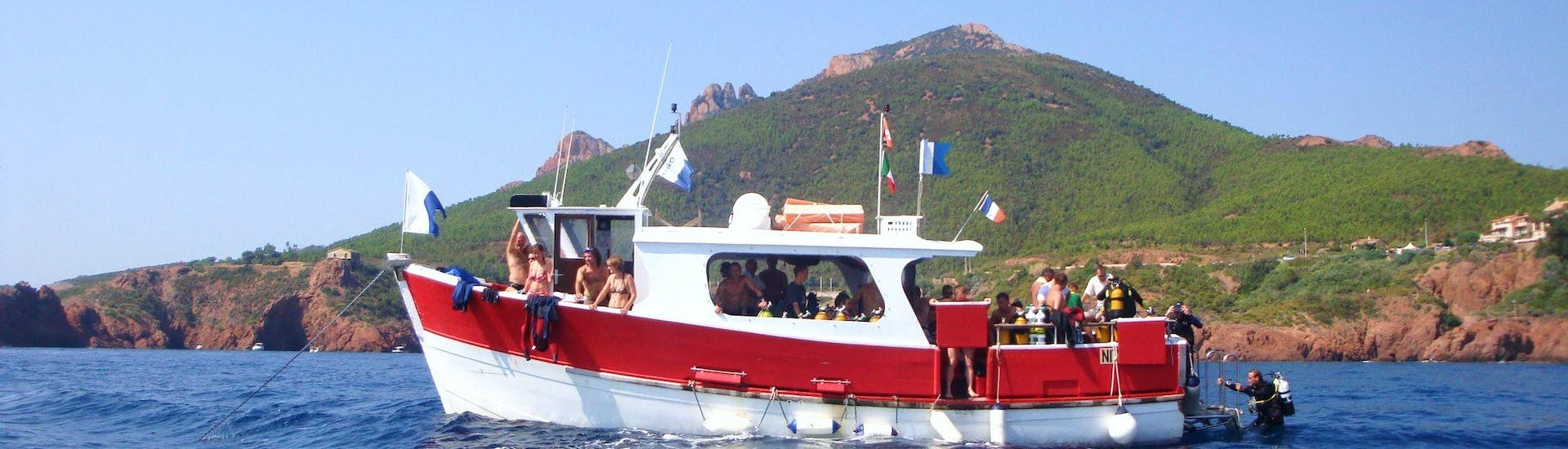 View of the Dive Center La Rague boat in front of the Estérel massif used for snorkeling trips and diving courses near Cannes.