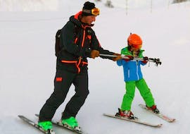 Ski instructor shows the child how to hold the ski sticks correctly during Private Ski Lessons for Kids - All Levels with the ski school Skibex.