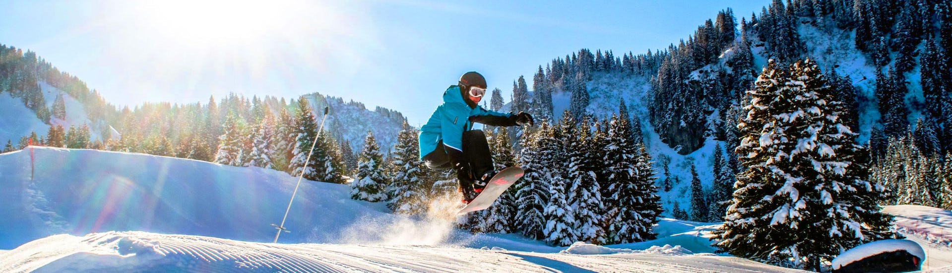 Snowboarder makes a jump in the snow-covered mountain landscape during his Private Snowboarding Lessons for Kids & Adults - All Levels with the Skibex ski school.