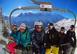 Adults sit in the chair lift to the top of the mountain for their Ski Lessons for Adults - 4 Day Duration (Sun-Wed) with the ski school Evolution 2 Chamonix.