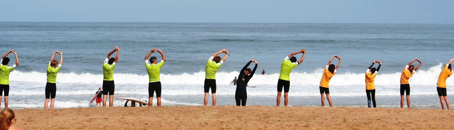 Surfers are warming up on the beach before the start of their Surfing Lessons on the Marinella Beach in Anglet with the surf school Le Club de la Glisse.
