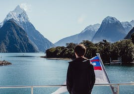 During the Coach Tour with Milford Sound Cruise - Vista Tour, a passenger is admiring the breathtaking views from a spacious modern catamaran operated by Jucy Cruise.