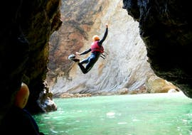"""A participant of the Coasteering """"Adventure"""" Tour in Sagres from Poseidon Adventure joyfully performs a jumping trick into the crystal clear water of the Atlantic."""