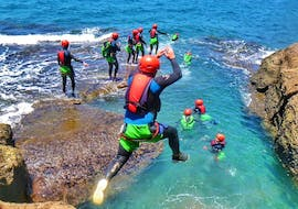 During the Coasteering at the South Coast of Gran Canaria, a man jumps from a rock into the crystal clear sea, under the supervision of a guide from Mojo Picón Aventura.