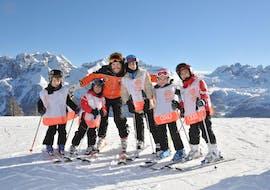 Children take group ski lessons