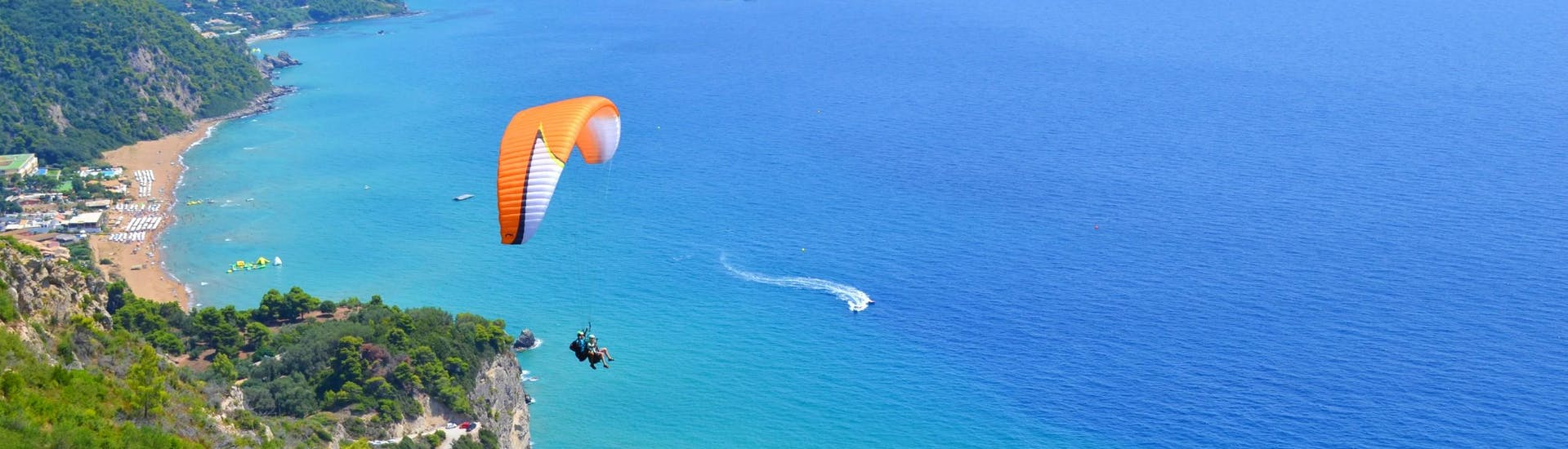 Atandem pilot from Corfu Paragliding and his passenger are gliding over the turquoise water of the Ionian Sea during a tandem flight.