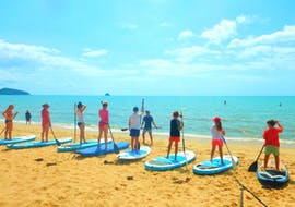 Our paddlers learning the basics on the beach during the Sunrise Stand Up Paddle Boarding Group Lesson in Cairns with Pacific Watersports