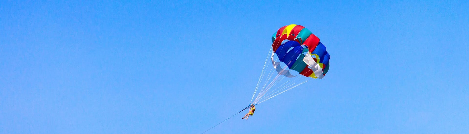A man is enjoying the magnificent 360 degree views whilst parasailing with Crazy Sports in Santorini.