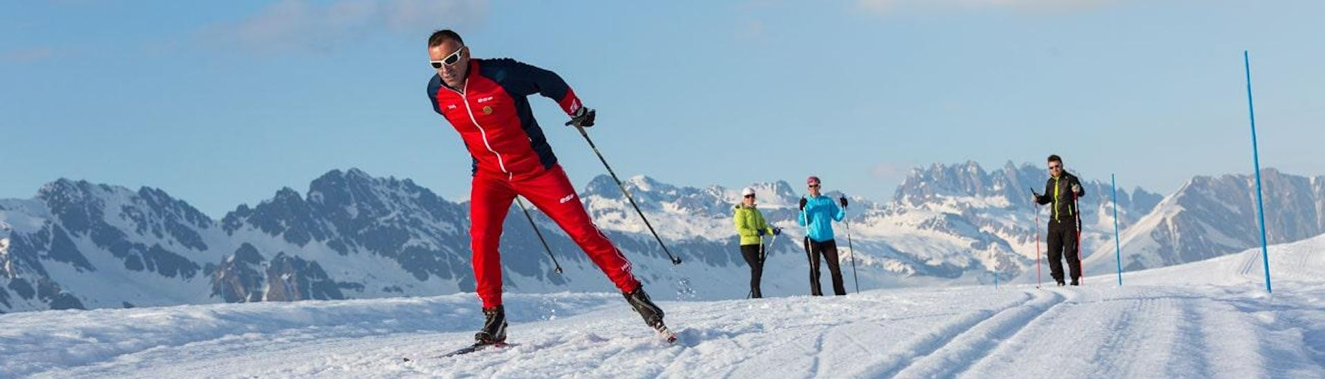 Two skiers are observing their cross-country skiing instructor of the ski school ESF Chamonix during their Cross-Country Skiing Lessons for Adults - All Levels.